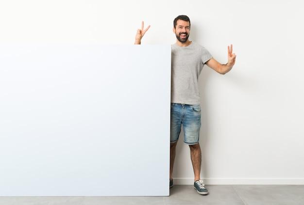 Junger gutaussehender mann mit dem bart, der ein großes blaues leeres plakat zeigt siegeszeichen mit beiden händen hält