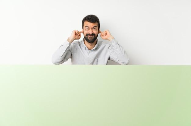 Junger gutaussehender mann mit dem bart, der ein großes grünes leeres plakat frustriert hält und ohren bedeckt