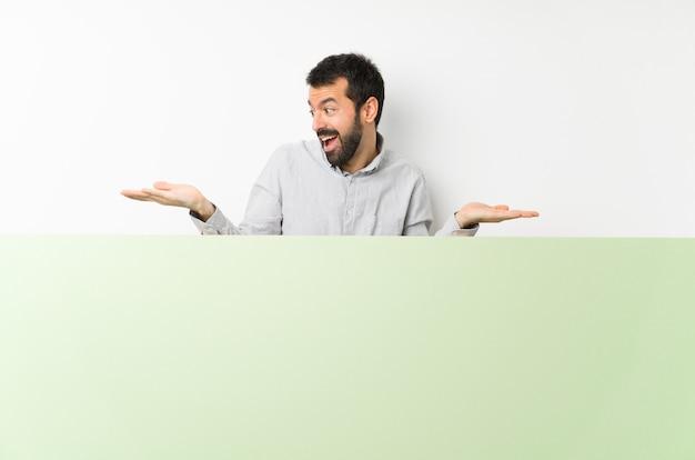 Junger gutaussehender mann mit dem bart, der ein großes grünes leeres plakat hält copyspace mit zwei händen hält