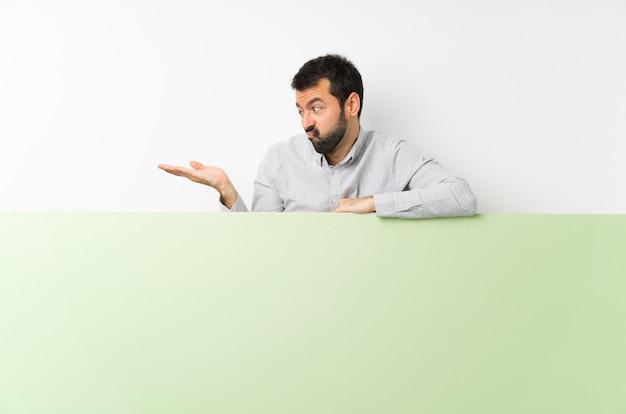 Junger gutaussehender mann mit dem bart, der ein großes grünes leeres plakat hält copyspace mit zweifeln hält