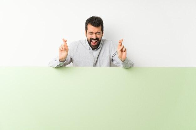 Junger gutaussehender mann mit dem bart, der ein großes grünes leeres plakat mit der fingerüberfahrt hält