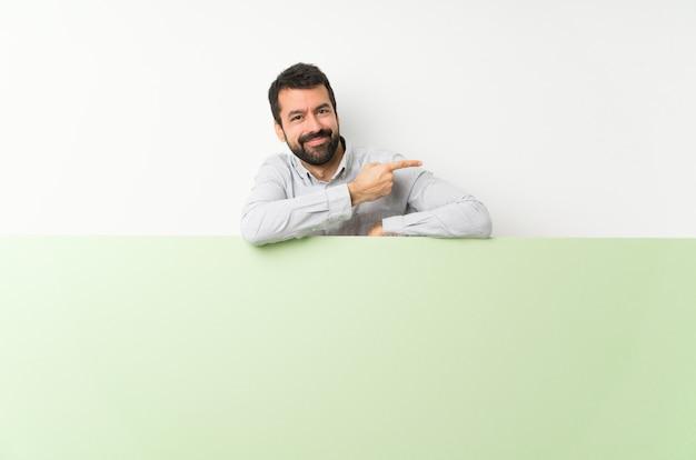 Junger gutaussehender mann mit dem bart, der ein großes grünes leeres plakat zeigt finger auf die seite hält