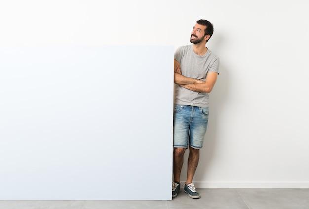 Junger gutaussehender mann mit dem bart, der ein großes leeres plakat beim lächeln oben schaut hält