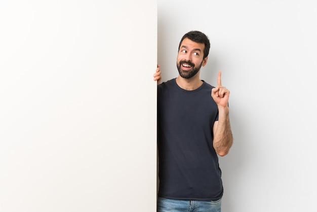 Junger gutaussehender mann mit dem bart, der ein großes leeres plakat denkt eine idee oben zeigt den finger hält
