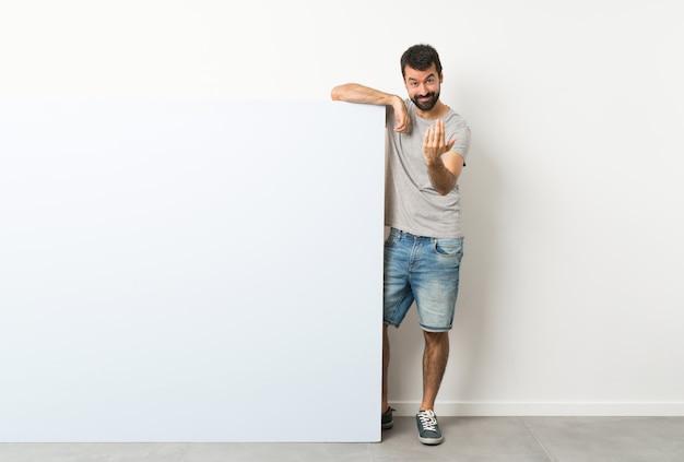 Junger gutaussehender mann mit dem bart, der ein großes leeres plakat einlädt, mit der hand zu kommen hält