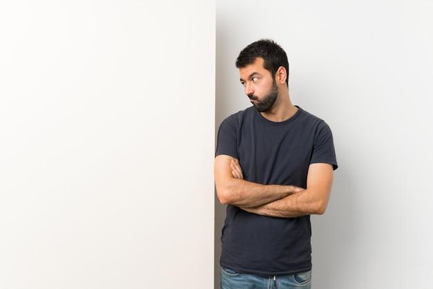 Junger gutaussehender mann mit dem bart, der ein großes leeres plakat glaubt umzukippen hält