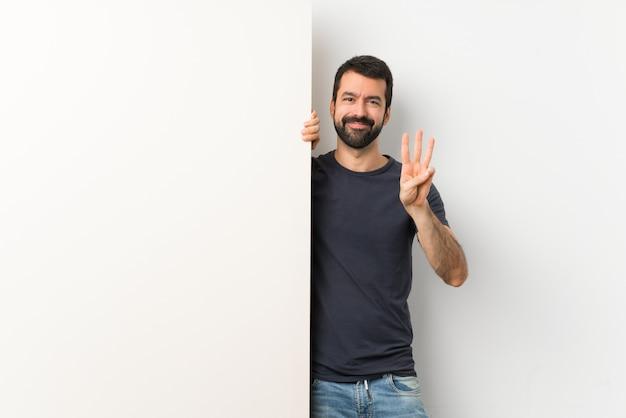 Junger gutaussehender mann mit dem bart, der ein großes leeres plakat glücklich hält und drei mit den fingern zählt