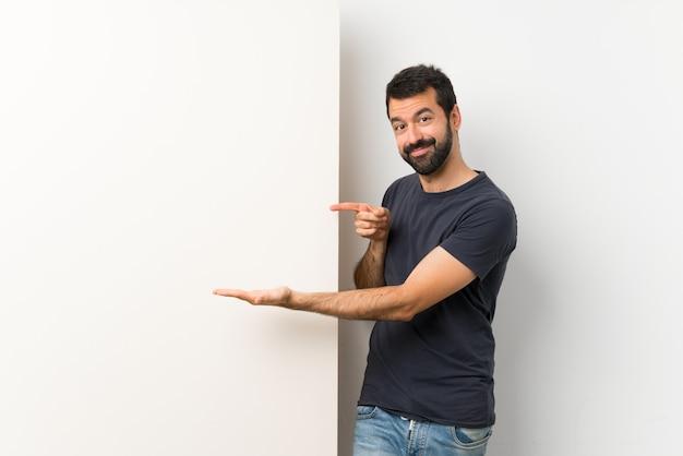 Junger gutaussehender mann mit dem bart, der ein großes leeres plakat hält copyspace eingebildet auf der palme hält, um eine anzeige einzufügen