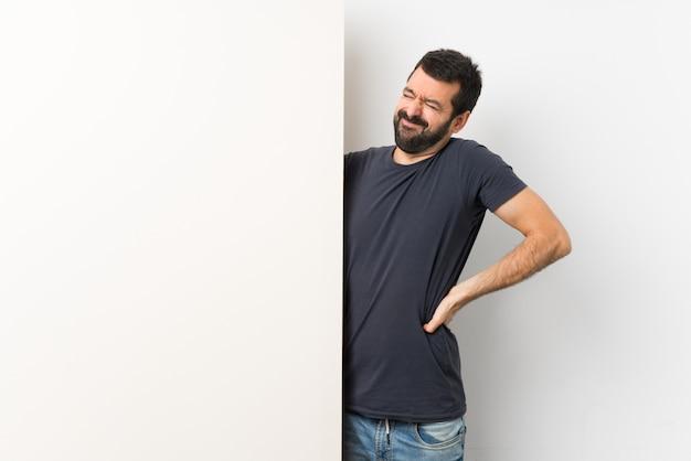 Junger gutaussehender mann mit dem bart, der ein großes leeres plakat hält