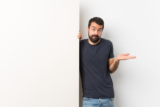 Junger gutaussehender mann mit dem bart, der ein großes leeres plakat hat zweifel beim anheben von händen hält