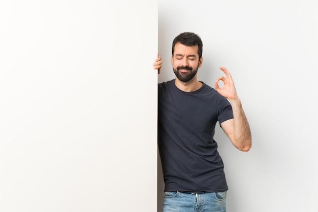 Junger gutaussehender mann mit dem bart, der ein großes leeres plakat in der zenhaltung hält