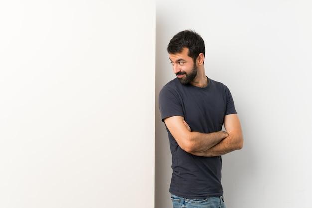 Junger gutaussehender mann mit dem bart, der ein großes leeres plakat mit den armen gekreuzt und glücklich hält