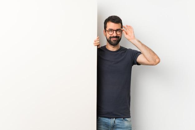 Junger gutaussehender mann mit dem bart, der ein großes leeres plakat mit gläsern und glücklich hält