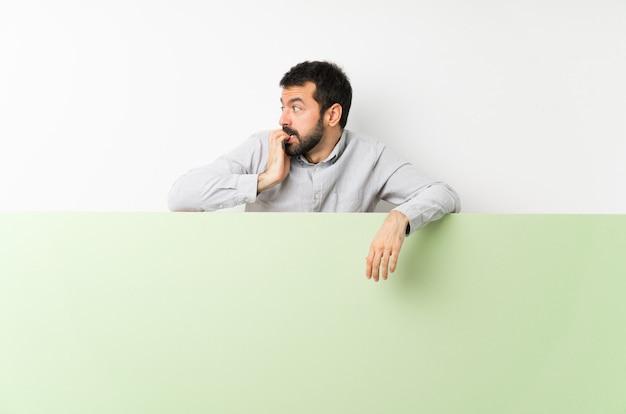 Junger gutaussehender mann mit dem bart, der ein großes leeres plakat nervös und erschrocken hält