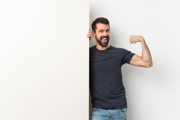 Junger gutaussehender mann mit dem bart, der ein großes leeres plakat tut starke geste hält