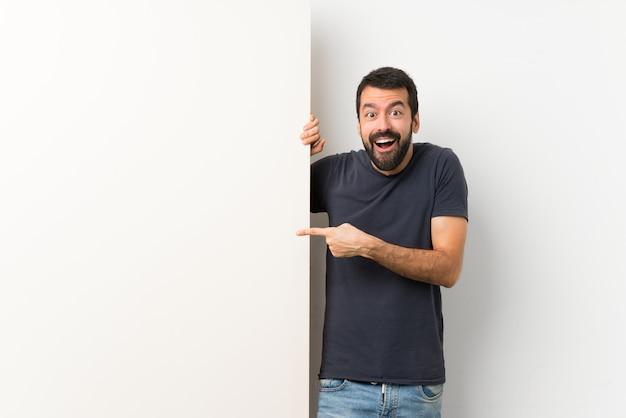 Junger gutaussehender mann mit dem bart, der ein großes leeres plakat überrascht hält und finger auf die seite zeigt