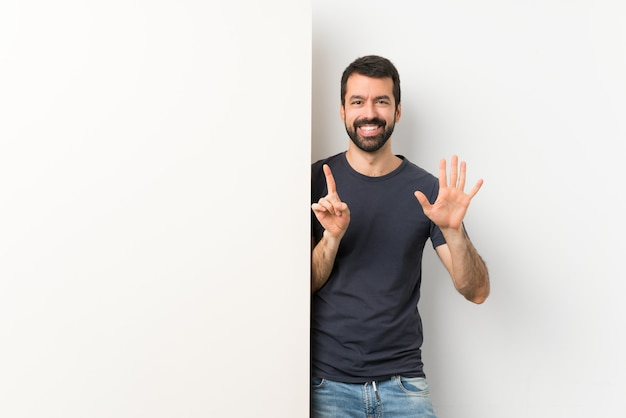 Junger gutaussehender mann mit dem bart, der ein großes leeres plakat zählt sechs mit den fingern hält