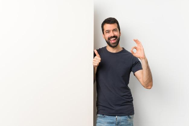 Junger gutaussehender mann mit dem bart, der ein großes leeres plakat zeigt okayzeichen und daumen herauf geste hält