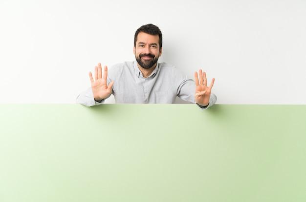 Junger gutaussehender mann mit dem bart, der ein plakat zählt neun mit den fingern hält