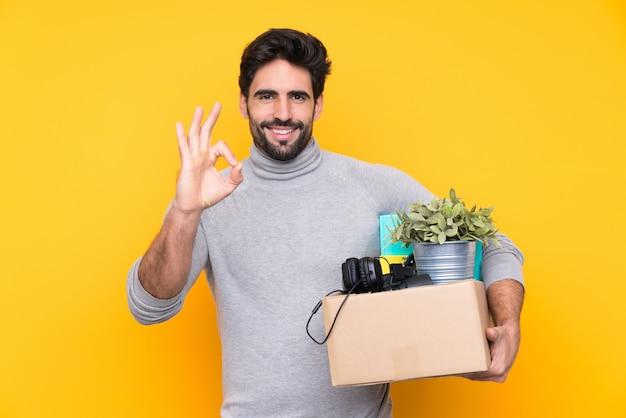 Junger gutaussehender mann mit dem bart, der eine bewegung beim einen kasten von sachen über der lokalisierten wand voll aufheben zeigt okayzeichen mit den fingern macht