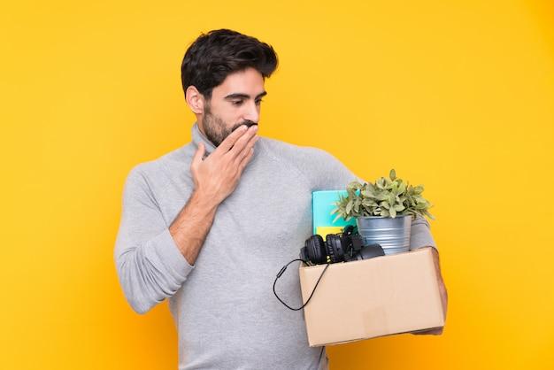 Junger gutaussehender mann mit dem bart, der eine bewegung beim einen kasten von sachen über lokalisierter wand mit überraschung und entsetztem gesichtsausdruck voll aufheben macht