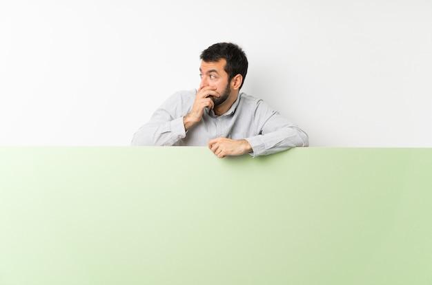 Junger gutaussehender mann mit dem bart, der einen großen grünen leeren plakatbedeckungsmund hält und zur seite schaut