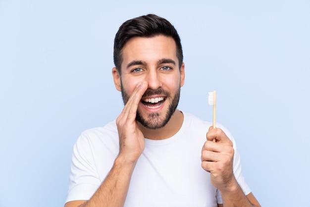 Junger gutaussehender mann mit dem bart, der seine zähne schreit mit dem breiten mund putzt, öffnen sich