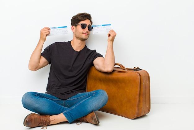 Junger gutaussehender mann mit den karten einer bordkarte, die auf dem boden in einem reinraum sitzen