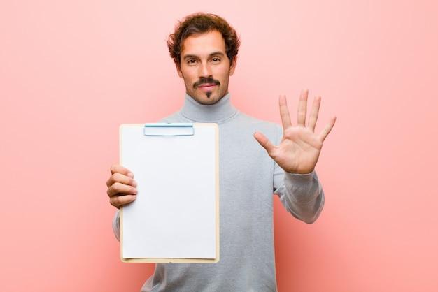 Junger gutaussehender mann mit einem blatt papier gegen rosa flache wand