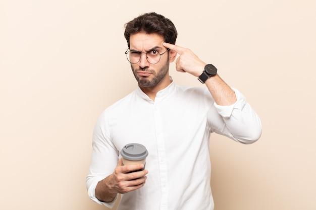Junger gutaussehender mann mit einem ernsten und konzentrierten blick, brainstorming und nachdenken über ein herausforderndes problem