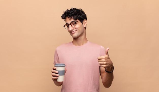 Junger gutaussehender mann mit einem kaffee, der stolz, sorglos, selbstbewusst und glücklich fühlt und positiv mit daumen hoch lächelt