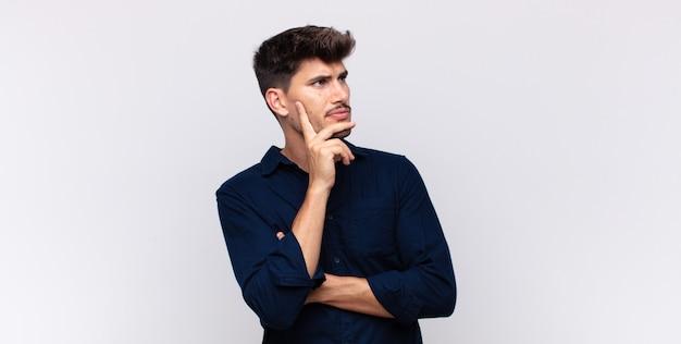 Junger gutaussehender mann mit einem konzentrierten blick, der sich mit einem zweifelhaften ausdruck wundert, aufblickend und zur seite schauend