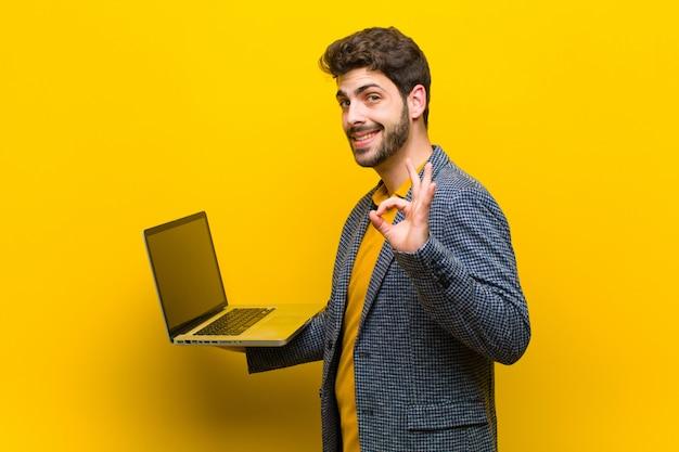 Junger gutaussehender mann mit einem laptop gegen orange
