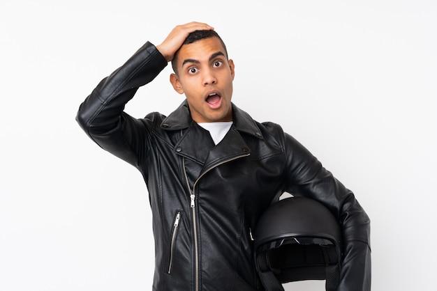 Junger gutaussehender mann mit einem motorradsturzhelm über lokalisierter weißer wand mit überraschungsgesichtsausdruck