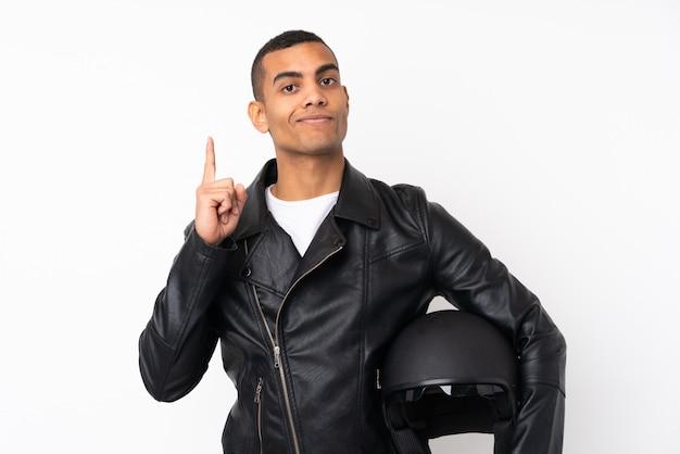 Junger gutaussehender mann mit einem motorradsturzhelm über lokalisierter weißer wand zeigend mit dem zeigefinger eine großartige idee