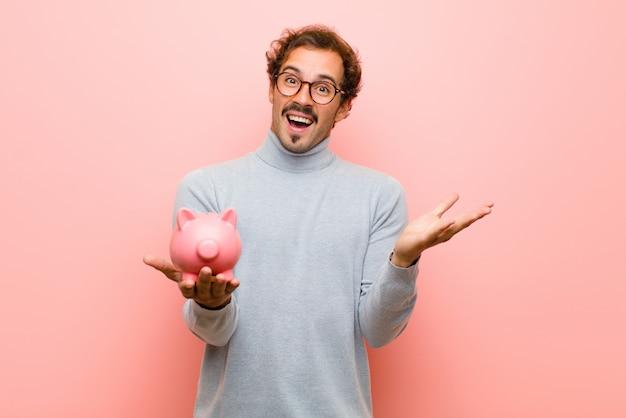 Junger gutaussehender mann mit einem sparschwein auf rosa flacher wand