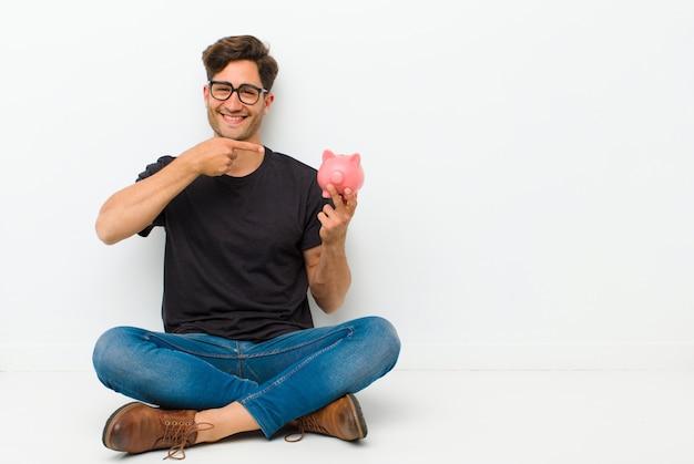 Junger gutaussehender mann mit einem sparschwein, das auf dem boden sitzt auf dem boden in einem reinraum sitzt