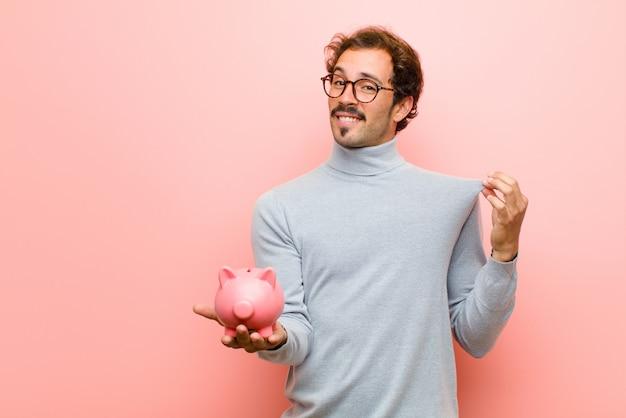 Junger gutaussehender mann mit einem sparschwein