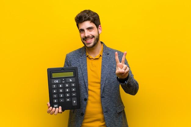 Junger gutaussehender mann mit einem taschenrechner