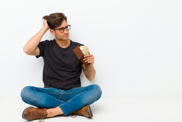 Junger gutaussehender mann mit einem und sitzen auf dem boden, der auf dem boden in einem reinraum sitzt