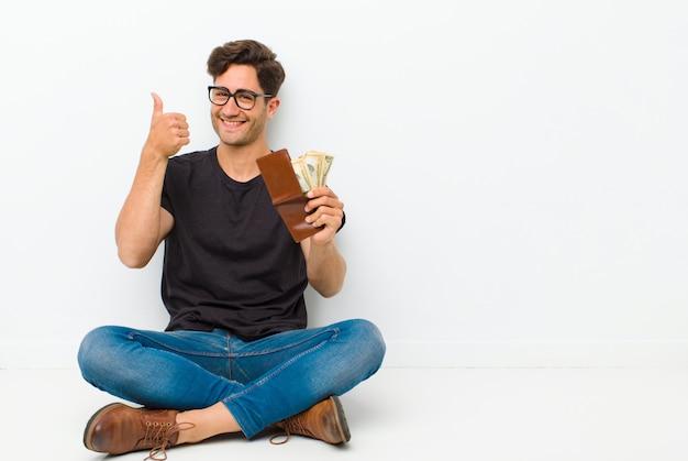 Junger gutaussehender mann mit einer geldbörse, die auf dem boden sitzt auf dem boden in einem reinraum sitzt