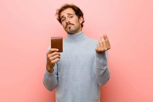 Junger gutaussehender mann mit einer geldbörse gegen rosa flache wand