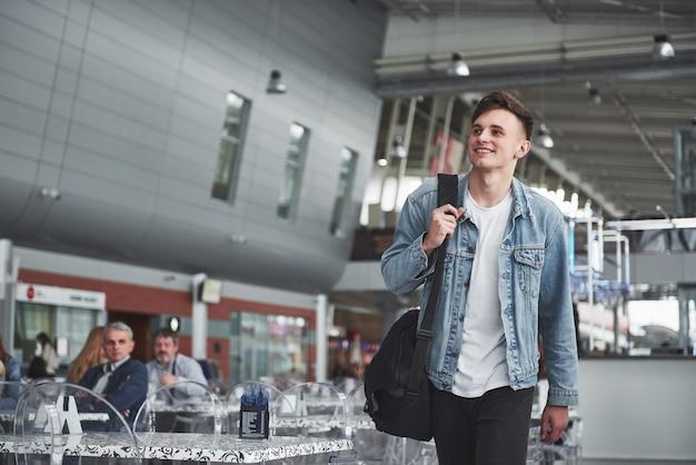 Junger gutaussehender mann mit einer tasche auf seiner schulter in eile zum flughafen.