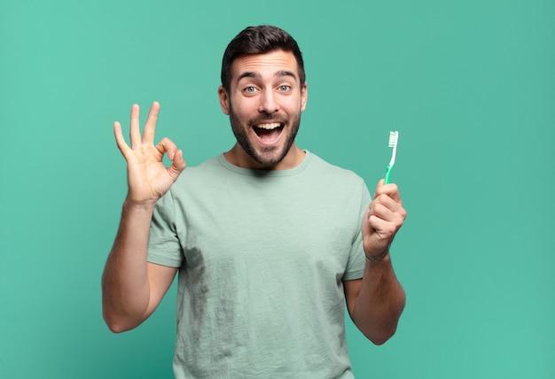 Junger gutaussehender mann mit einer zahnbürste.