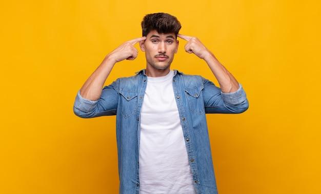 Junger gutaussehender mann mit ernstem und konzentriertem blick, brainstorming und nachdenken über ein herausforderndes problem