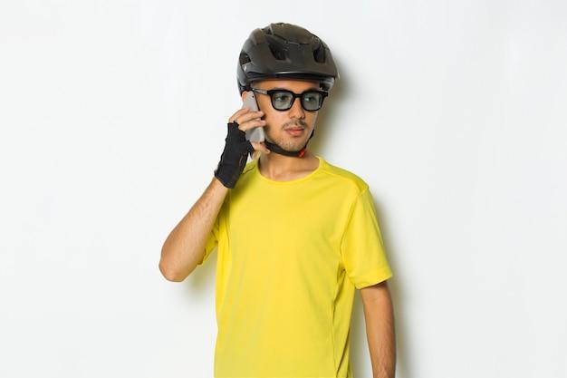 Junger gutaussehender mann mit fahrradhelm mit handy isoliert auf weißem hintergrund