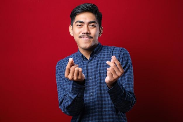 Junger gutaussehender mann mit freizeithemd auf rotem hintergrund, der geldgeste mit den händen macht und um gehaltszahlung bittet, millionärsgeschäft