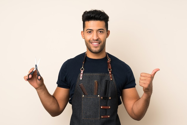 Junger gutaussehender mann mit friseur- oder friseurkleid mit dem daumen oben
