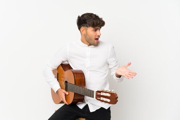 Junger gutaussehender mann mit gitarre mit überraschungsgesichtsausdruck