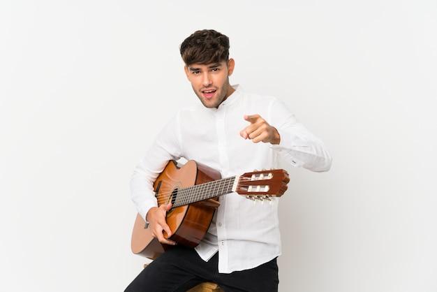 Junger gutaussehender mann mit gitarre überraschte und front zeigend